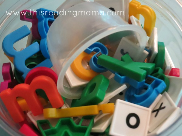letter tiles and magnetic letters dumped in a container together