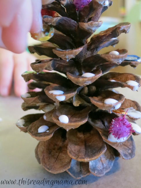 decorating the pine cone Christmas trees with pom-poms and sequins