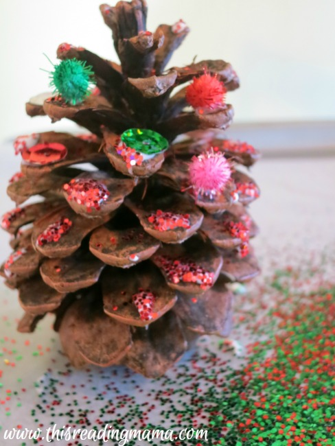 sprinkling glitter on pine cone Christmas trees
