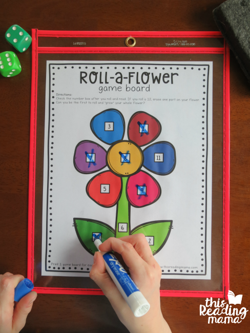 crossing off numbers on the roll a flower game board after rolling dice