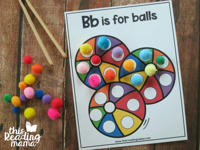 covering alphabet dot pages with pom-poms